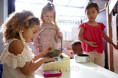 Three kindergarten schoolgirls playing shop in a playhouse at an infant school, backlit