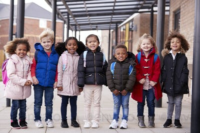 Group of smiling young multi-ethnic school kids standing in a walkway outside their infant school