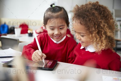 Close up of two kindergarten schoolgirls using a tablet computer and stylus