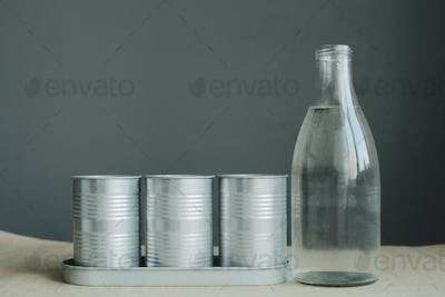 still life of glass bottle and metal pot