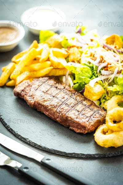 Grilled beef meat steak with french fries onion ring with sauce