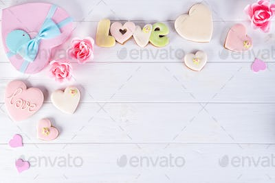 Valentines day gift boxes with heart shaped cookies and decorations on white wooden background