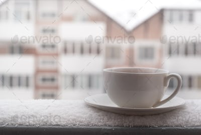 Cup of hot tea outdoor in snowing day.