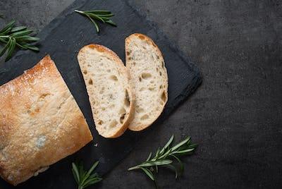 Italian ciabatta bread  on black slate with herbs and olives.