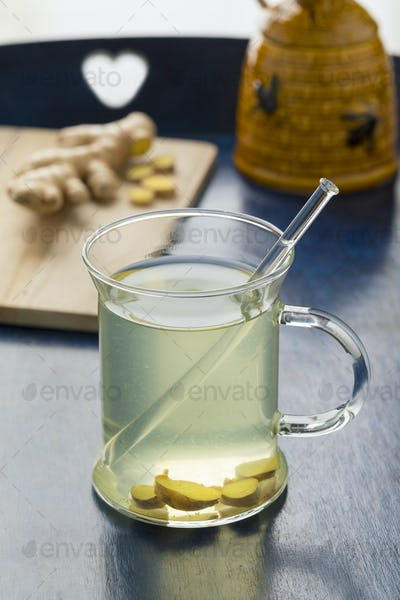 Glass cup with ginger tea and honey