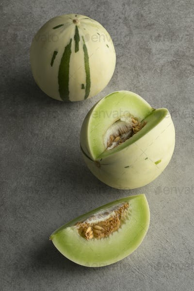 Whole and cut white honeydew melons