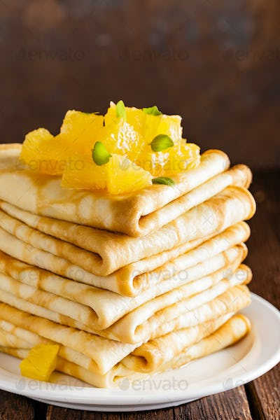 Homemade thin crepes with oranje jam, stack of pancakes on wooden rustic background