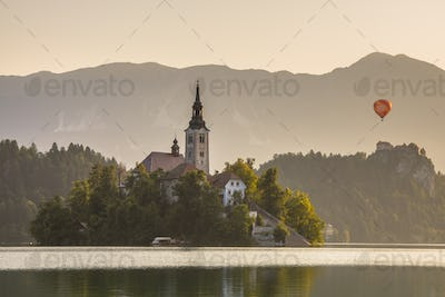 Island in lake Bled with orange hot air balloon