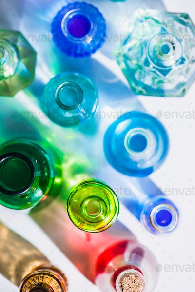 Glass bottle assortment with colorful shadows and flares on a white background with copy space