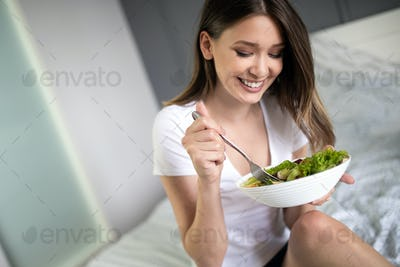 Beautiful woman eating healthy fresh organic salad