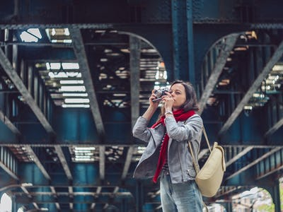 Young photographer with a retro photo camera on the street