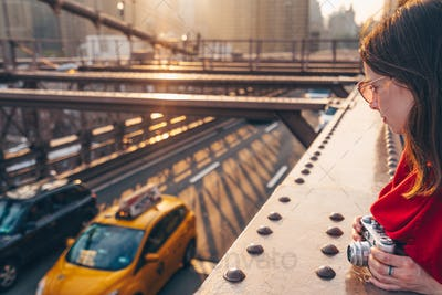Attractive girl with a camera on Brooklyn Bridge
