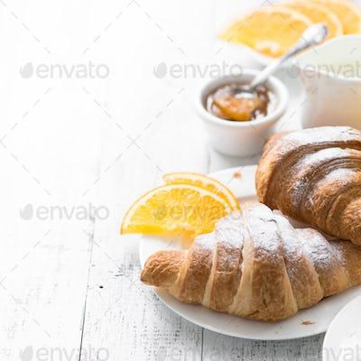 Croissant jam coffee orange jice at white wooden table.