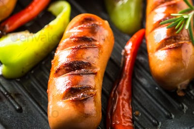 Fried sausages with  vegetables in grill pan at black background
