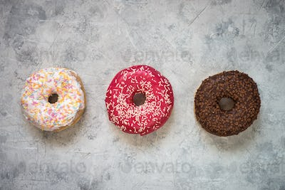 Colorful donuts at concrete table.