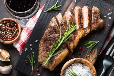 Grilled beef striploin steak with red wine glass.