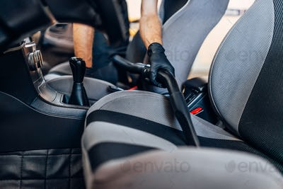 Auto detailing, cleaning seats with vacuum cleaner