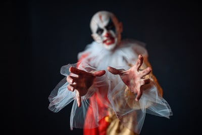 Bloody clown reaching for victim with his hands