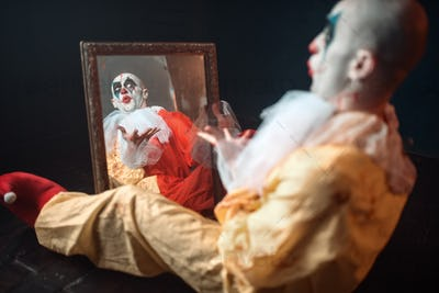 Bloody clown with crazy eyes sitting at the mirror