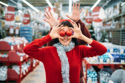 Couple chooses christmas tree balls in shop