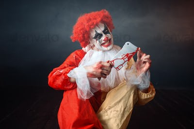 Bloody clown with crazy eyes looking on his knife