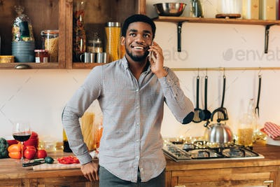 Young black man talking on mobile phone in kitchen