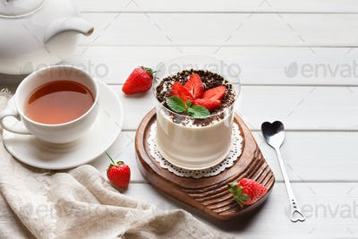 Panna cotta dessert with fresh strawberry on wooden table