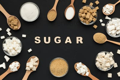 Various types of sugar on black background.