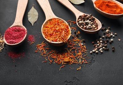 Saffron, peppercorns and sumac on dark table