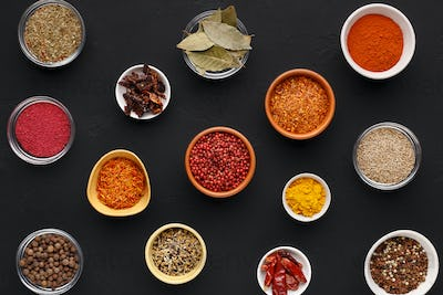 Assortment of spices in bowls on black background