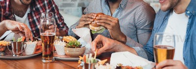 Three men enjoying burgers and beer in bar