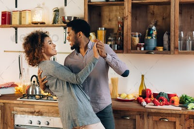 Young african-american couple dancing in kitchen, copy space
