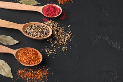 Colourful spices in wooden spoons on background