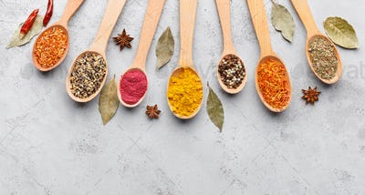 Colourful spices in wooden spoons on grey background