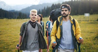 Gorup of friends climbing up hill, with backpacks and climbing stick
