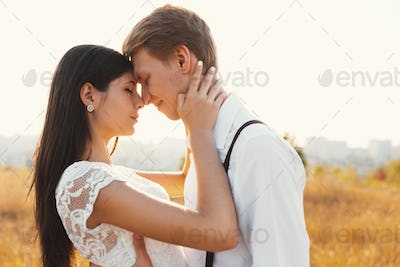 Loving couple dressed in white, ready to kiss outdoors with clos