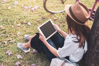 Young woman relaxing and using tablet and surf internet in the park