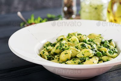 Conchiglie pasta with spinach and green pea pesto. Italian Cuisine. Vegan food.
