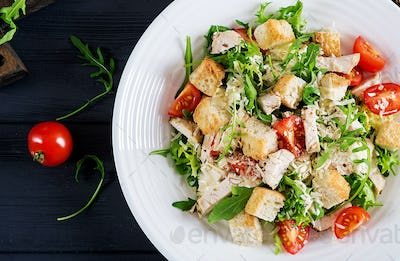 Healthy grilled chicken Caesar salad with tomatoes, cheese and croutons.
