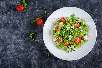 Dietary salad with tomatoes, blue cheese, avocado, arugula and pine nuts. Top view. Flat lay.