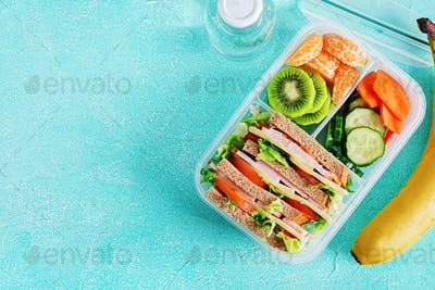 School lunch box with sandwich, vegetables, water, and fruits on table.