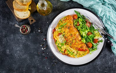 Breakfast. Omelette with tomatoes, avocado, blue cheese and green peas