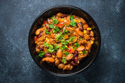 Chili con carne from meat and vegetables on black table top view
