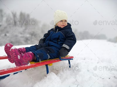 Little adorable girls enjoy a sleigh ride. Child sledding. Children play outdoors