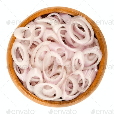 Rings of sliced shallots in wooden bowl over white