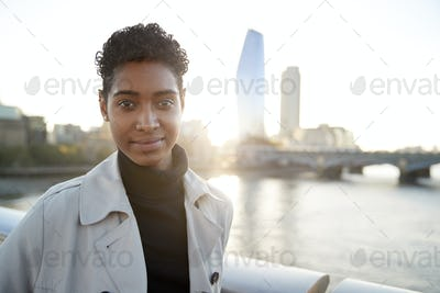 Young black woman  standing on Millennium Bridge, London, looking to camera smiling