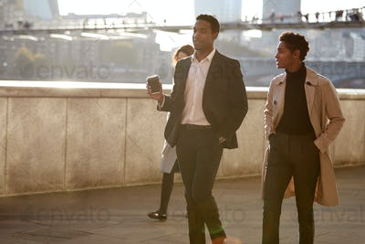 Two business colleagues walking by the Thames riverside in the city of London