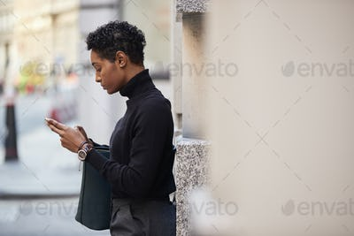 Young black woman standing on a street in London using her smartphone