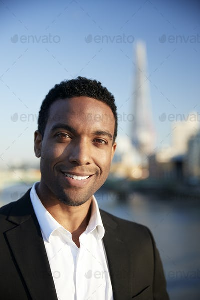 Young black businessman in smart casual clothing standing by the River Thames , Smiling