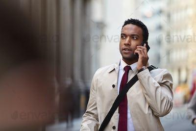 Millennial black businessman walking in a busy London street using smartphone, close up